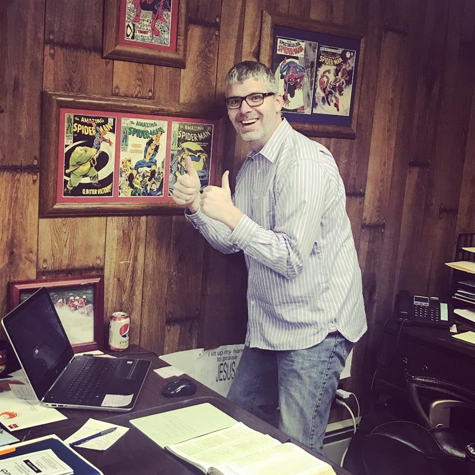 Pastor Ewing in his office with vintage comic books.